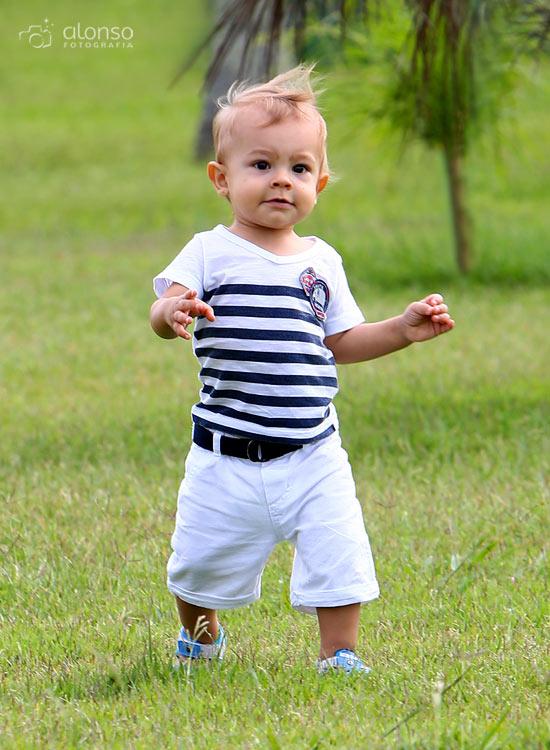 Bebê de um ano caminhando na grama