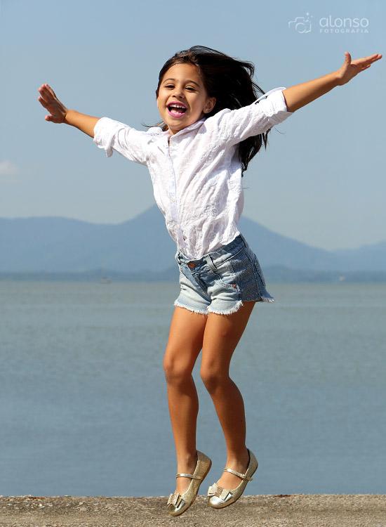 Criança pulando na praia book