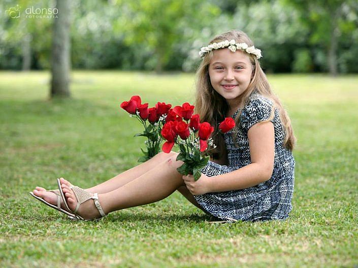Menina na grama com rosas vermelhas book